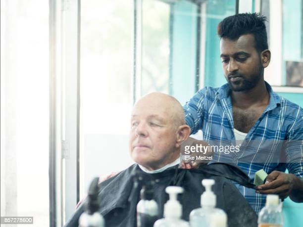 barber checking his work and removing gown