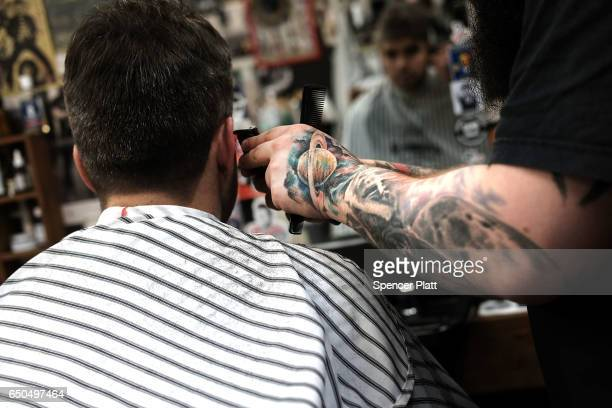 A barber cuts hair at Pomades one of numerous new barbershops in Moscow that caters to a growing hipster clientele on March 9 2017 in Moscow Russia...