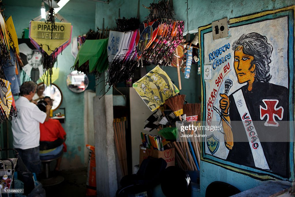 A barber cuts the hair of a client besides a huge portrait of legendary Vasco da Gama player Roberto Carlos at the Complexo do Alemao favela on June 29, 2013 in Rio de Janeiro, Brazil. It was at the end of 2010 that under the stage of pacification some 300 police officers went into the Complexo do Alemao with tanks and helicopters to drive out the criminal gangs to establish a permanent police presences and to set up social services such as schools, healthcare centers, and rubbish collection. The Complexo do Alemao favela is, with a population of 100, 000 and stretching for more than 3 kilometers with a maze of narrow alleys and stairways, one of the largest favelas in Rio de Janeiro.