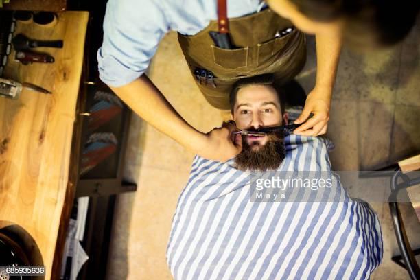 Barber cutting a beard