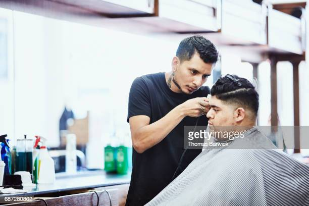 Barber cutting clients hair in barber shop