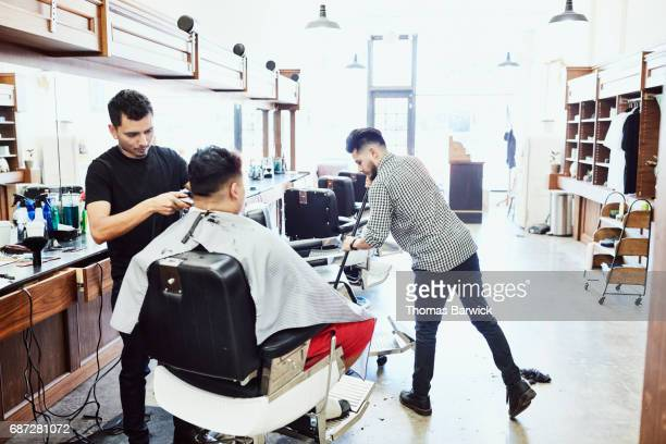Barber cutting clients hair in barber shop while coworker sweeps the floor