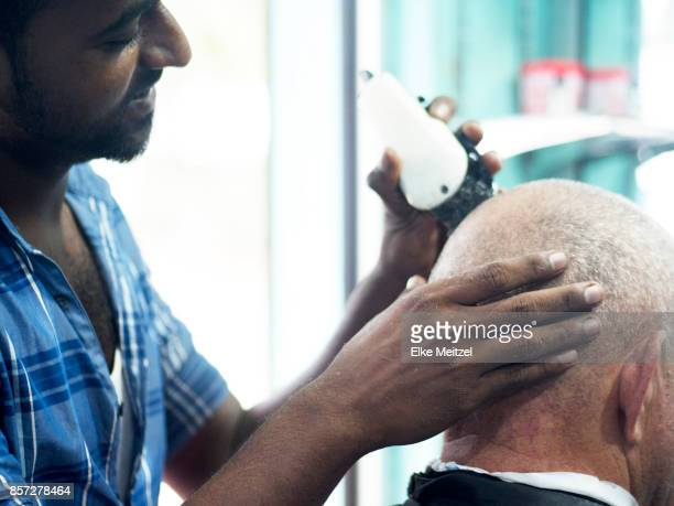 barber cutting clients hair with shaver tool