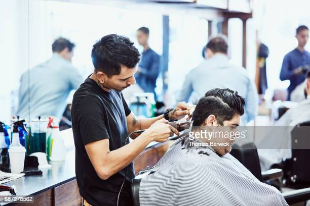 Barber cutting clients hair with trimmers