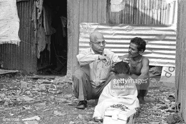 Barber cutting hair of boy in slum, Bombay Mumbai, Maharashtra, India