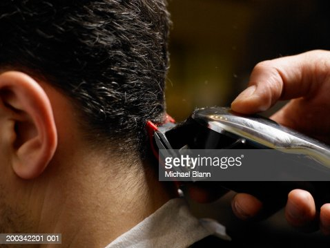 Barber cutting man's hair, close-up of electric razor, side view