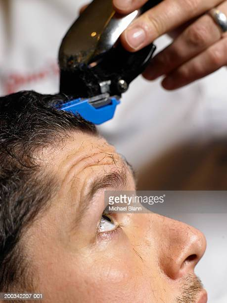 Barber cutting man's hair with electric razor, profile, close-up