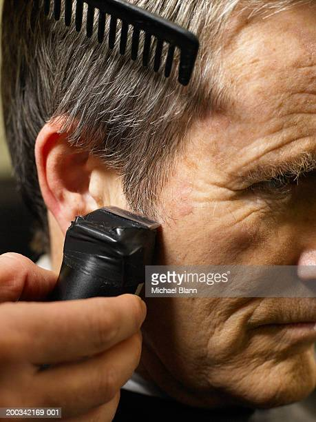 Barber cutting senior man's hair, close-up of electric razor