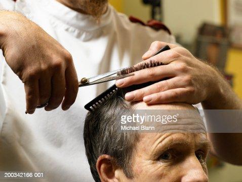 Barber cutting senior man's hair, close-up of hands