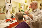 Barber cutting senior man's hair in barbershop