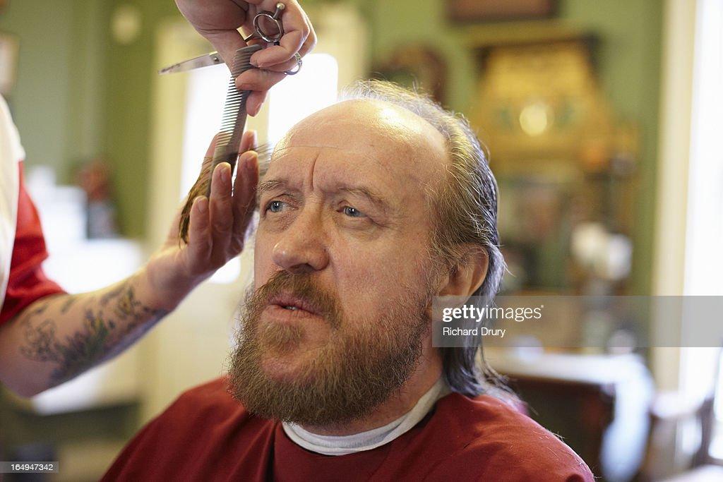 Barber cutting senior man's hair : Stock Photo