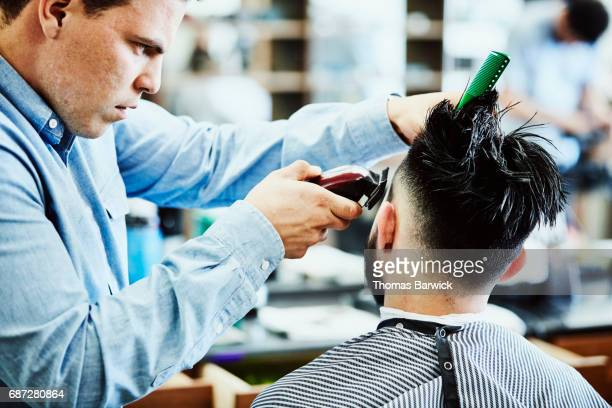 Barber cutting side of clients hair with trimmers in barber shop