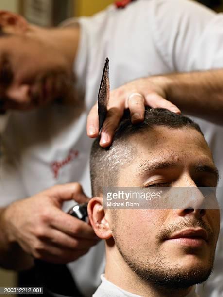 Barber giving man haircut, focus on man
