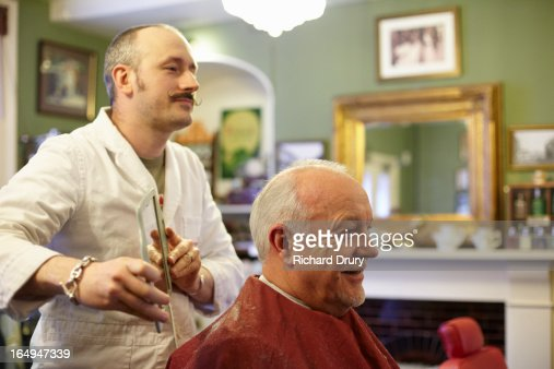 Barber holding mirror to show customer haircut