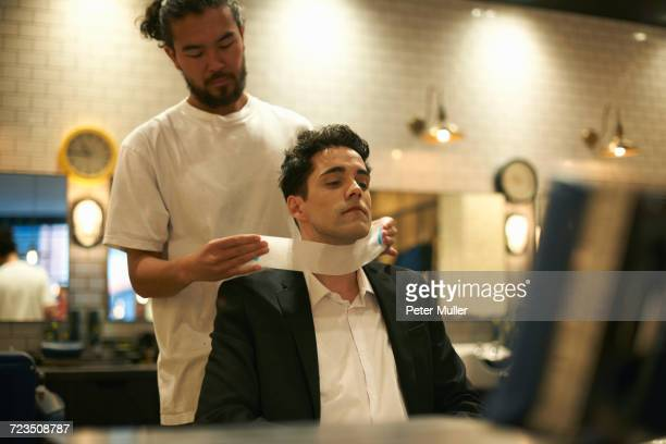 Barber preparing businessman for shave in barber shop