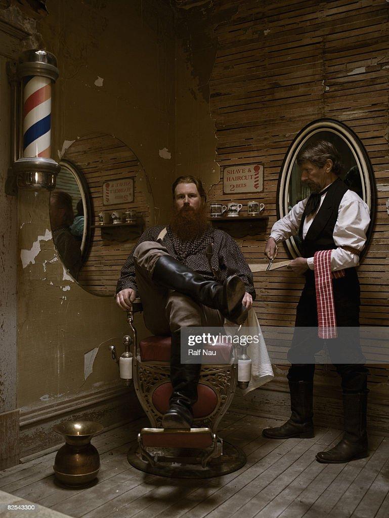Barber sharpening blade before shaving man's beard : Stock Photo