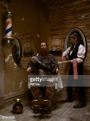 Barber sharpening blade before shaving man's beard : Foto de stock