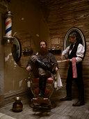 Barber sharpening blade before shaving man's beard