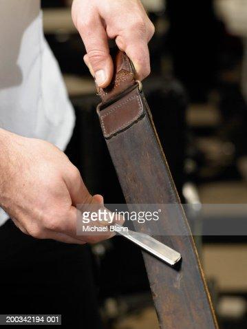 Barber sharpening razor blade on leather strip, close-up of hands : Foto de stock