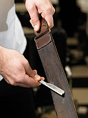 Barber sharpening razor blade on leather strip, close-up of hands