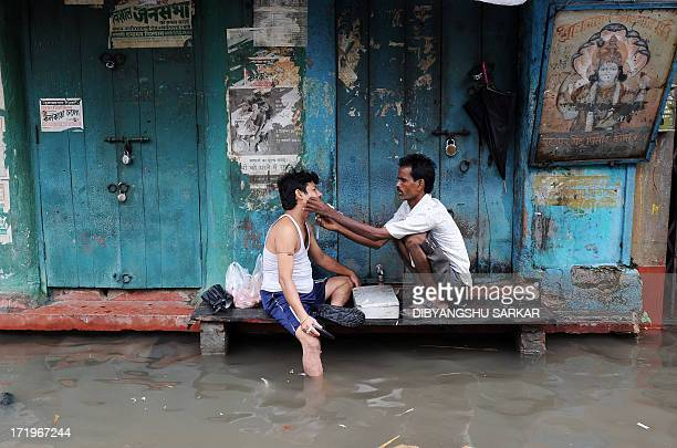 A barber shaves a customer in his temporary shop alongside a waterlogged street in Kolkata on June 30 2013 Heavy rains in various parts of Kolkata...