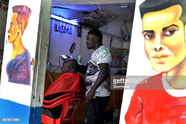 A barber shaves a customer's head at his shop in the Toi market in the outskirts of Kibera slum in Nairobi Kenya on Tuesday Aug 15 2017 Kenyan...