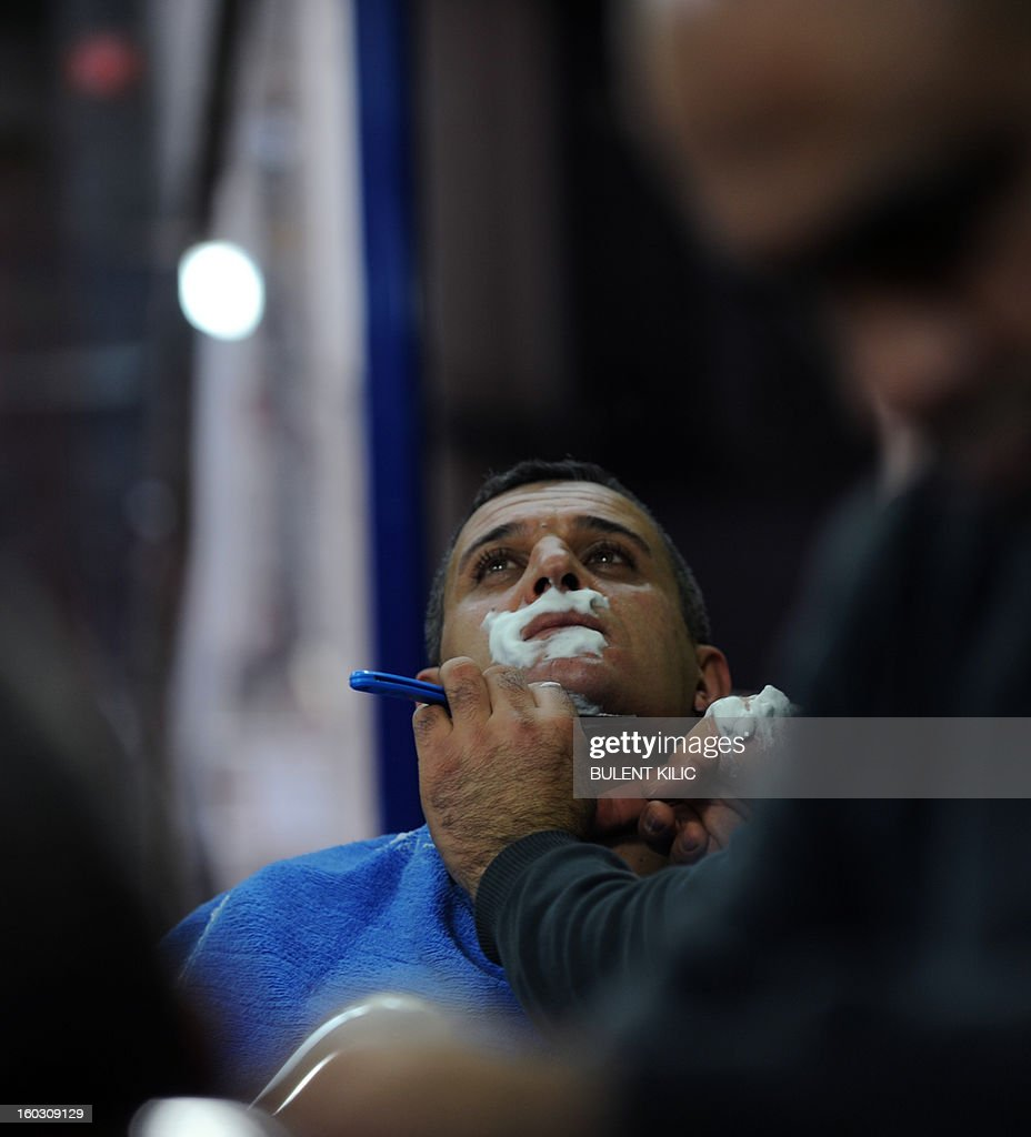 A barber shaves a man on January 25, 2013, in Istanbul.