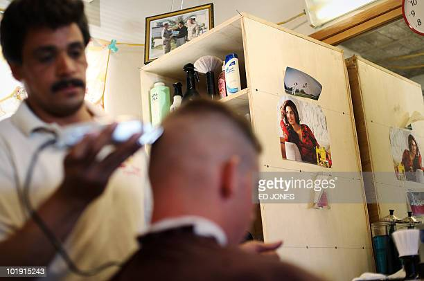 A barber shaves a US soldier's head at Camp Nathan Smith in Kandahar city on June 9 2010 NATO US and Afghan soldiers are preparing their biggest...