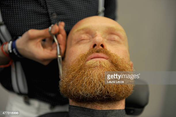 A barber shaves a visitor during the Pitti Uomo 88 at Fortezza da Basso on June 16 2015 in Florence Italy