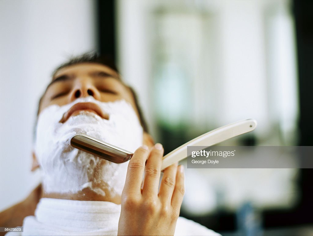 barber shaving a young man : Stock Photo