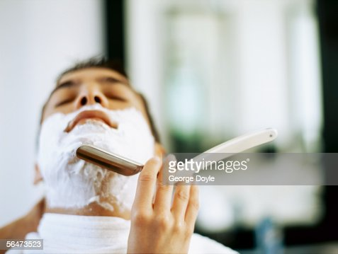barber shaving a young man : Foto de stock