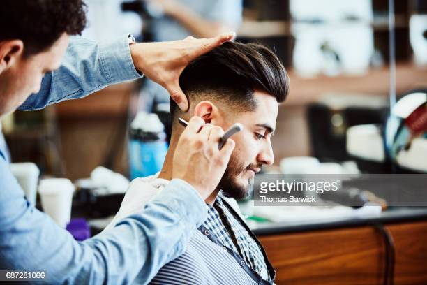 Barber shaving back of clients neck with straight razor after hair cut in barber shop