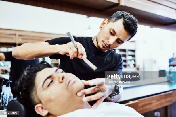 Barber shaving client with straight razor in barber shop