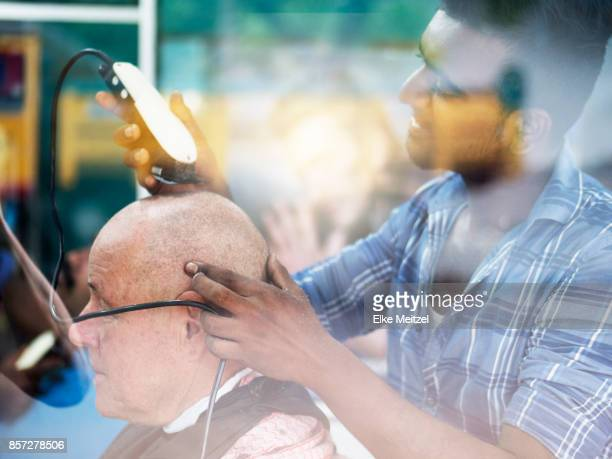 barber shaving clients head