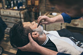 Barber shaving customers beard in vintage barber shop