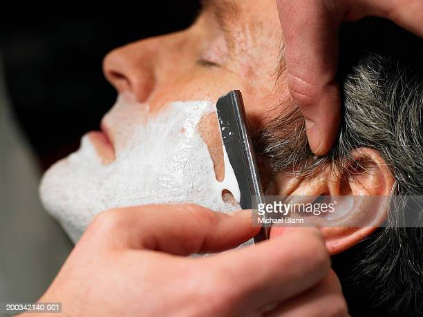Barber shaving senior man, close-up