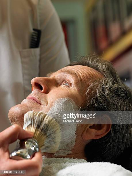 Barber shaving senior man