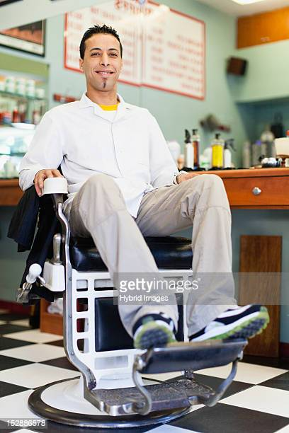 Barber sitting in chair in shop