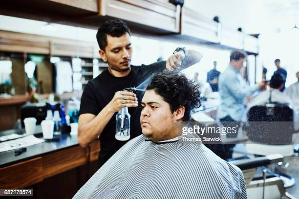 Barber spraying water while combing out clients hair