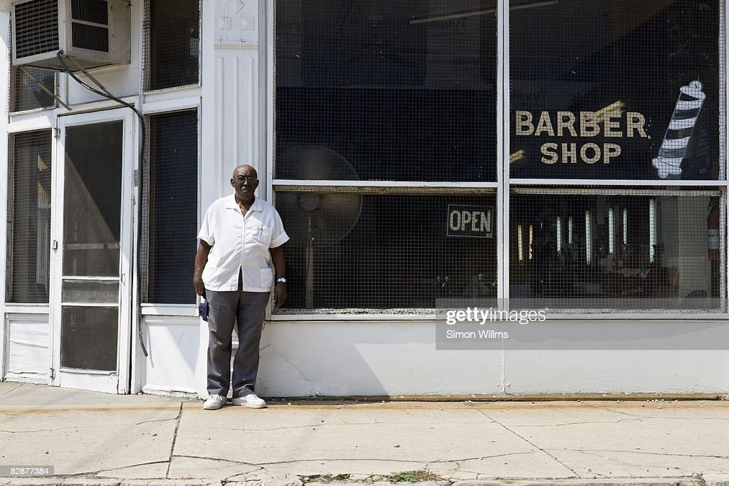 Barber standing in front of his barber shop : Stock Photo