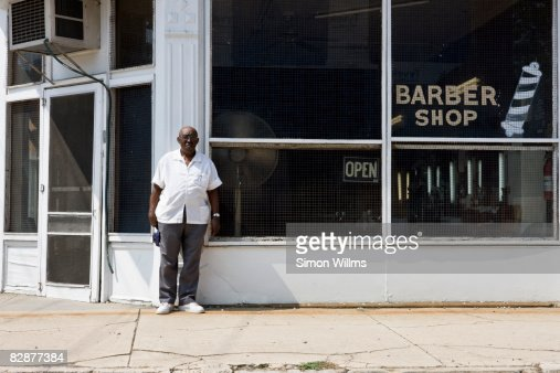 Barber standing in front of his barber shop : Foto de stock