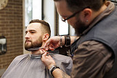Barber styling beard with scissors at barbershop. Stylish hairdresser in male hair salon