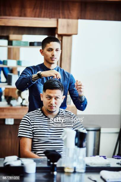 Barber styling clients hair after hair cut in barber shop