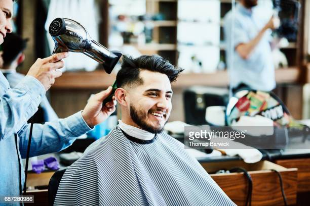 Barber styling smiling clients hair after hair cut in barber shop