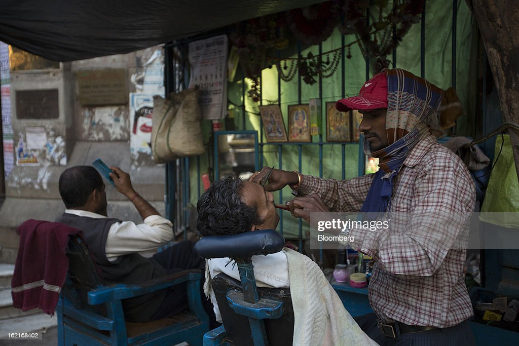 A barber tends to a customer in Kolkata, India, on Tuesday, Feb. 19, 2013. India's slowest economic expansion in a decade is limiting profit growth at the biggest companies even as foreigners remain net buyers of the nation's stocks, according to Kotak Institutional Equities. Photographer: Brent Lewin/Bloomberg via Getty Images
