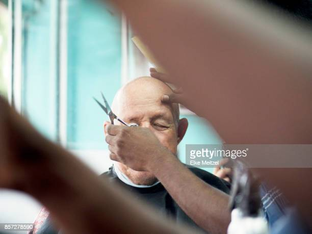 barber trimming clients eye brows