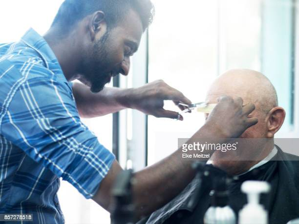 barber trimming clients eyes brows