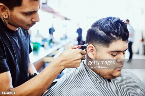Barber trimming mans hair in barber shop