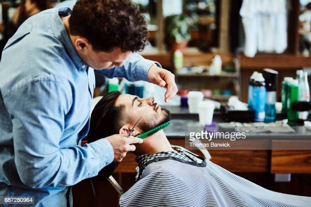 Barber trimming up clients beard after shave in barber shop