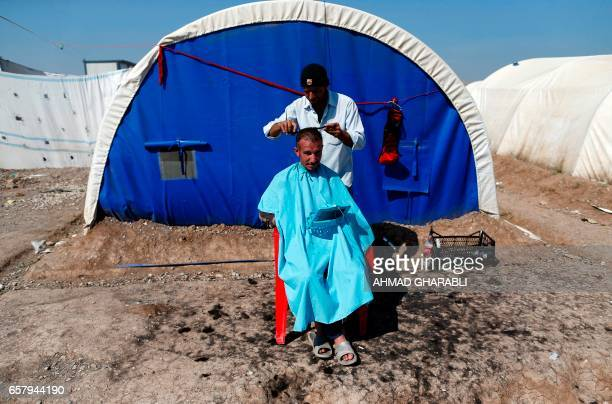 TOPSHOT A barber trims the hair of a displaced Iraqi who fled the violence in the northern city of Mosul as a result of a planned operation to retake...